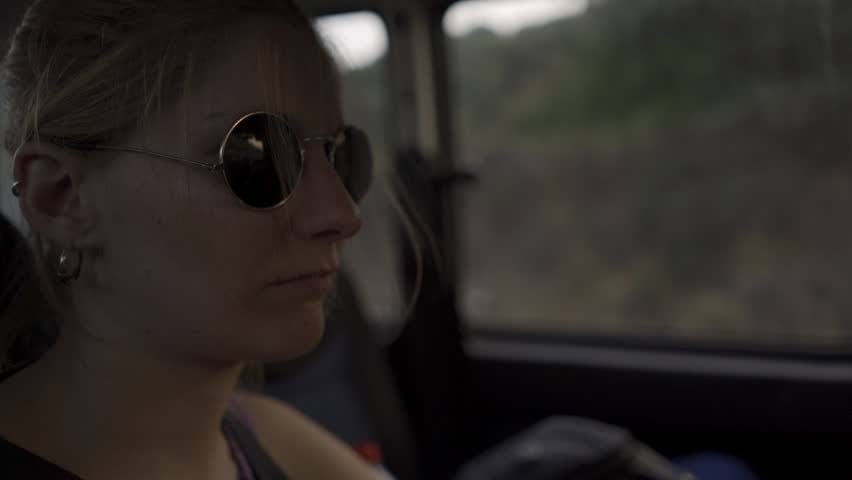 Young woman with sunglasses traveling in the back seats of a car at sunset  #1018005040