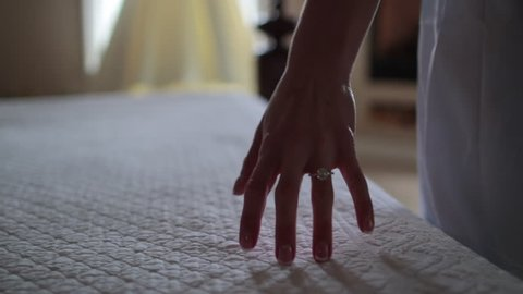 Close up of hand caressing bed towards dress