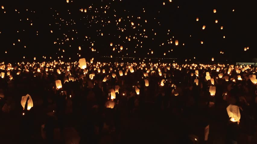 Drone footage of thousands of glowing lanterns flying across screen. Beautiful floating lanterns light the night sky as thousands of people gather to let their wishes fly. #1018036390
