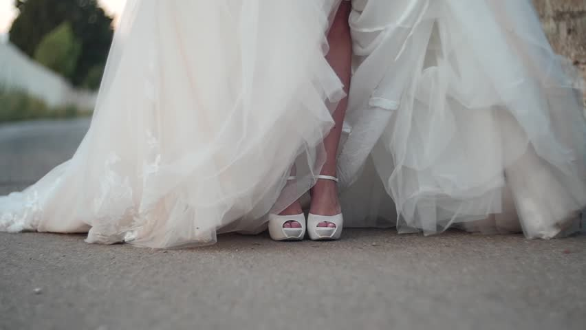 Low angle view of a bride's feet on her wedding day. At first the bride stands still and then starts running. You see the white shoes and the white wedding dress with the folds of the dress.  | Shutterstock HD Video #1018056100