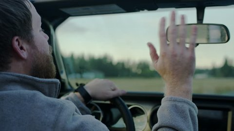 Closeup Of Dad Driving, He Adjusts His Rear View Mirror And Waves To Child In Back Seat, Slow Motion