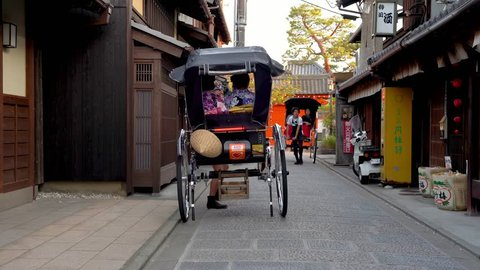 Kyoto, JAPAN - APRIL 18, 2018: pulled rickshaw driver working hard and introducing the Japanese temple to the passengers