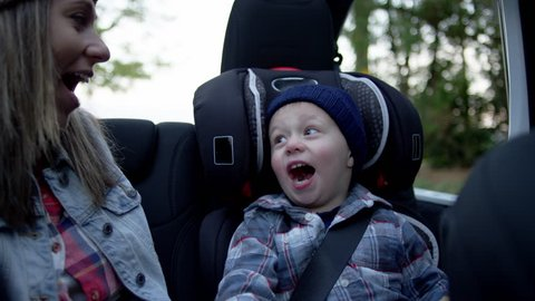 Mom Sits In Back Seat Of Jeep With Top Off, She Whispers A Secret To Her Little Boy, He Makes A Surprised Face And They Laugh, Slow Motion