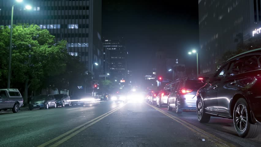 Night city traffic. 4K time lapse of a busy city street and cars driving leaving light trails | Shutterstock HD Video #1018165570