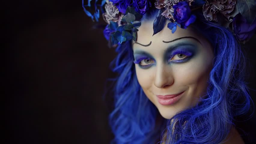 Halloween face art. Portrait of a beautiful woman looking at the camera and smiling, makeup the bride's corpse. Blue accents on hair and eyes, black background