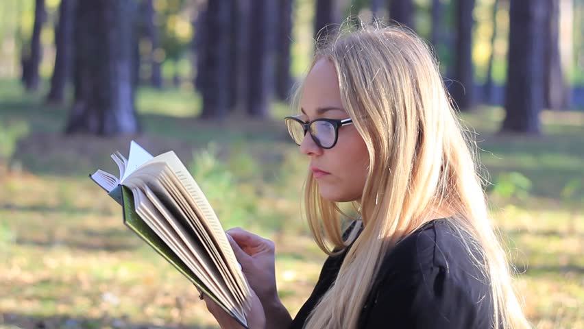 beautiful girl with glasses reading a book
