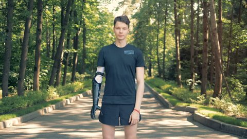 A young man with bionic arm in park. Futuristic human cyborg concept.