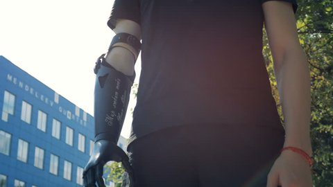 A man with a modern bionic prosthetic arm is standing in city. Future concept.