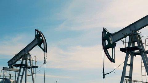 Oil pumps working on a field. Metal oil derricks work, pumping oil.