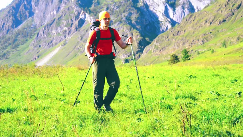 FHD Hiking man walking on green mountain meadow with backpack. Tourist travelling in sunny outdoors. Summer sport and recreation concept. | Shutterstock HD Video #1018195300