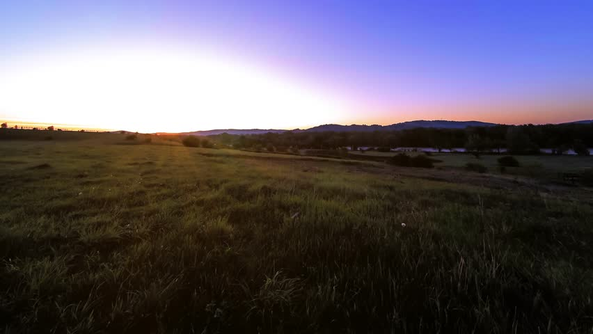4K UHD mountain meadow timelapse at the summer or autumn time. Wild nature and rural field. Clouds, trees, green grass and sun rays movement. | Shutterstock HD Video #1018195420