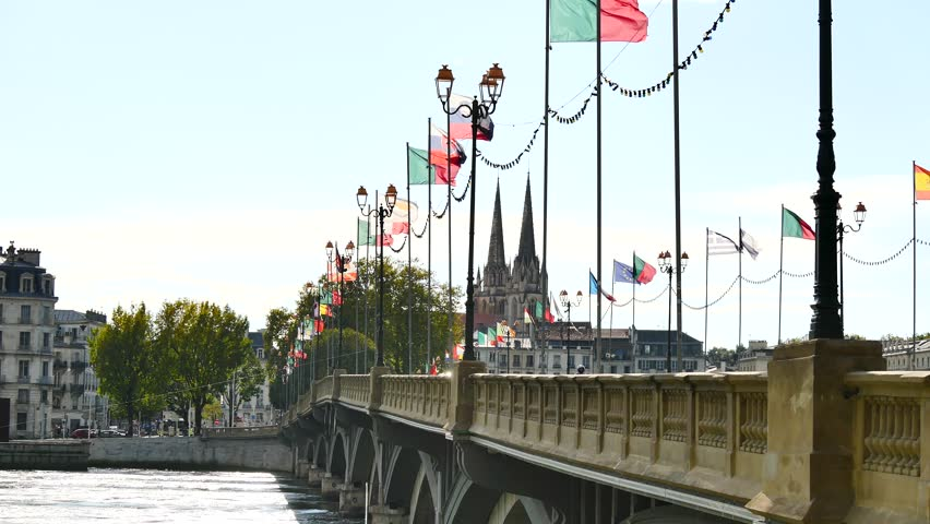 View of the Pont Saint-Esprit, in the city of Bayonne, in southwestern France. This bridge crosses the Adour River to reach the city centre. There are a lot of flags hanging on the bridge. | Shutterstock HD Video #1018201960