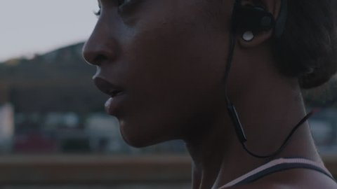 close up attractive young african american runner athlete running in urban city exercising healthy fitness lifestyle