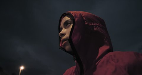 young woman runner ready for intense exercise running training in city at night wearing hood close up