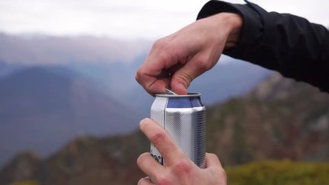 Man opens can of beer