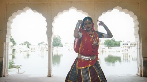 A mid shot of a graceful and attractive dancer in traditional colorful cloths or attire performing in beautiful palace against the lake. An Indian classical or folk dancer dancing in ancient mansion