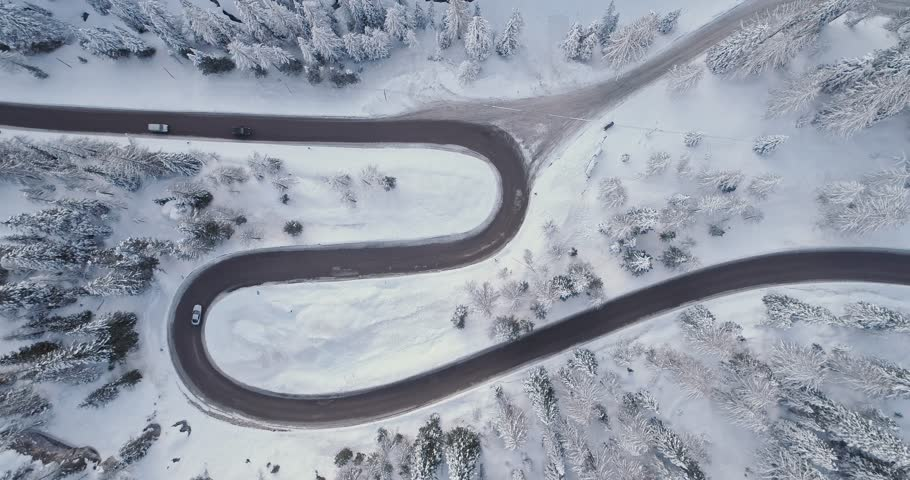 Overhead vertical aerial above hairpin turn road with cars,woods snowy forest.Sunset or sunrise.Winter Dolomites Italian Alps mountains outdoor nature establisher.4k drone flight establishing shot | Shutterstock HD Video #1018368250