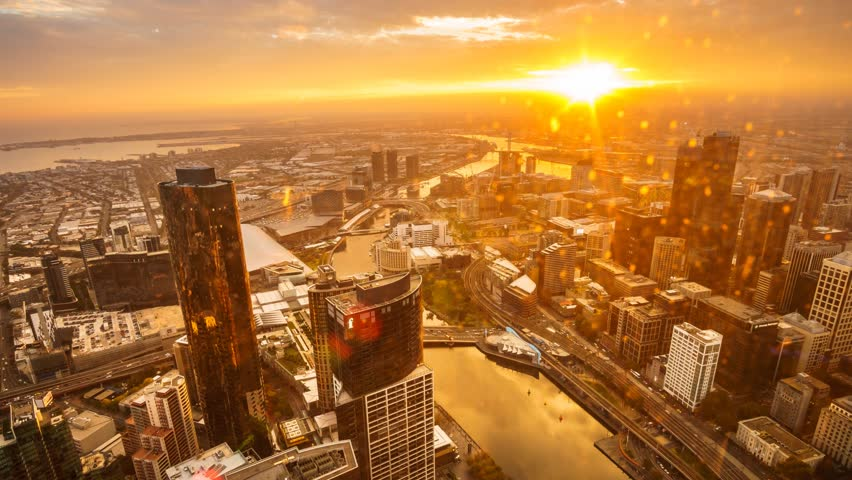 An aerial view of Melbourne cityscape including Yarra River and Victoria Harbour in the distance. Timelapse during sunset with beautiful sun ray bursting through fast moving clouds. Timelapse Zoom In. #10183700