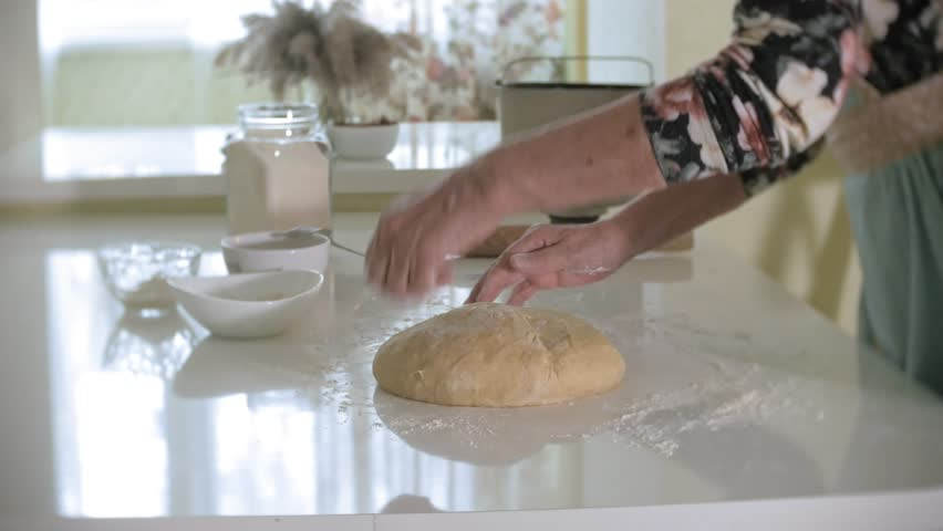 Happy senior woman rolling pizza dough at home in the kitchen 4k #1018412170