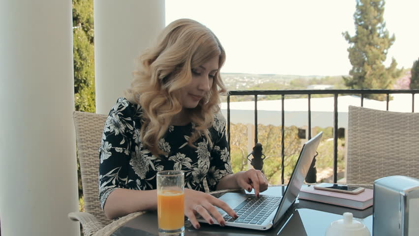 Attractive young woman working at laptop in a cafe on the terrace | Shutterstock HD Video #10184210