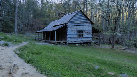 GATLINBURG, TENNESSEE / UNITED STATES - APRIL 21, 2016: Stable dynamic shot of rustic log cabin in The Great Smoky Mountains National Park on cool day as camera moves toward house along foot path.