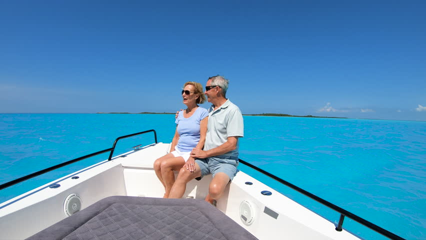Healthy Caucasian American seniors in casual clothing resting on luxury sail boat spending their retirement on turquoise ocean Bahamas USA   Shutterstock HD Video #1018446850