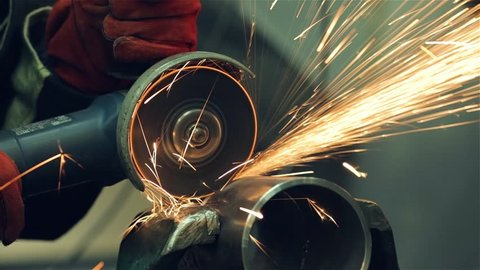 A red-gloved locksmith cleans a welded seam on a section of a steel pipe with the help of a grinding machine in the metal workshop