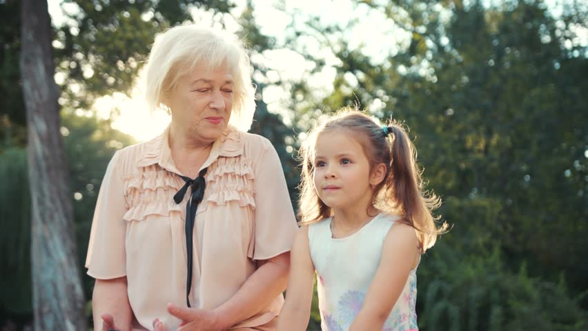 Cheerful Caucasian old lady looking after nice little girl. Lovely Slavic grandmother hugging granddaughter. Summertime. Park. Outdoors | Shutterstock HD Video #1018479850