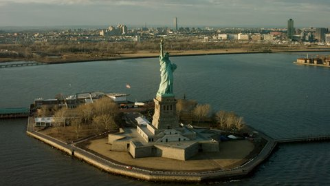 Aerial pan of Upper Bay water to the Statue of Liberty monument and Manhattan skyline, New York City, bright winter day lighting. Wide shot on 4k RED camera.