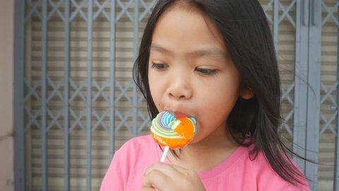 Beautiful asian little girl with lollipop