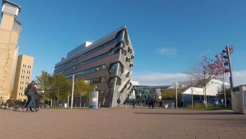 Coventry, West Midlands, UK - October 26, 2018: Coventry university pedestrian area with the engineering building and library with students walking through