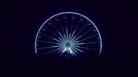 Ferris wheel runs in the night, illuminated by the lights