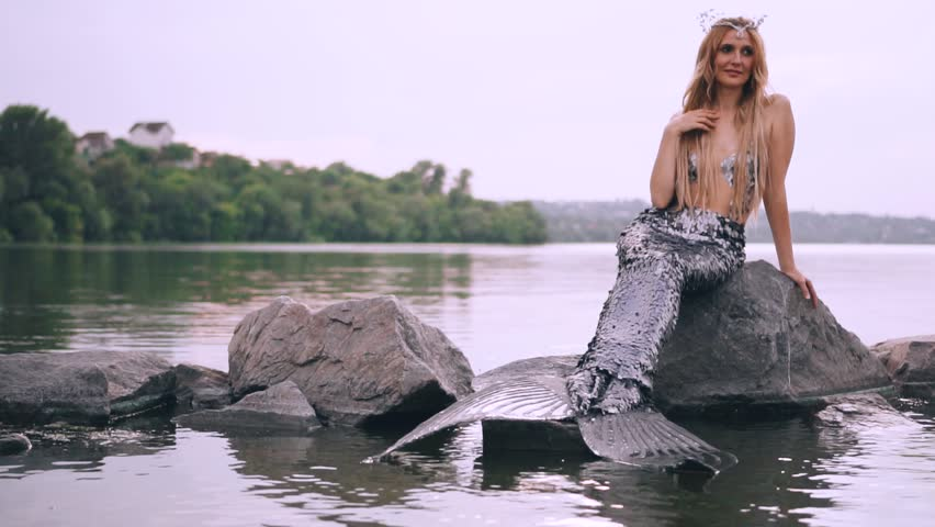 Sympathetic aquatic woman, a sea maiden with blond hair and a long tail sits on a stone in the lake and dreams of a prince when splashes of water fly past her, a summer creative video | Shutterstock HD Video #1018558840