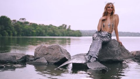 sympathetic aquatic woman, a sea maiden with blond hair and a long tail sits on a stone in the lake and dreams of a prince when splashes of water fly past her, a summer creative video