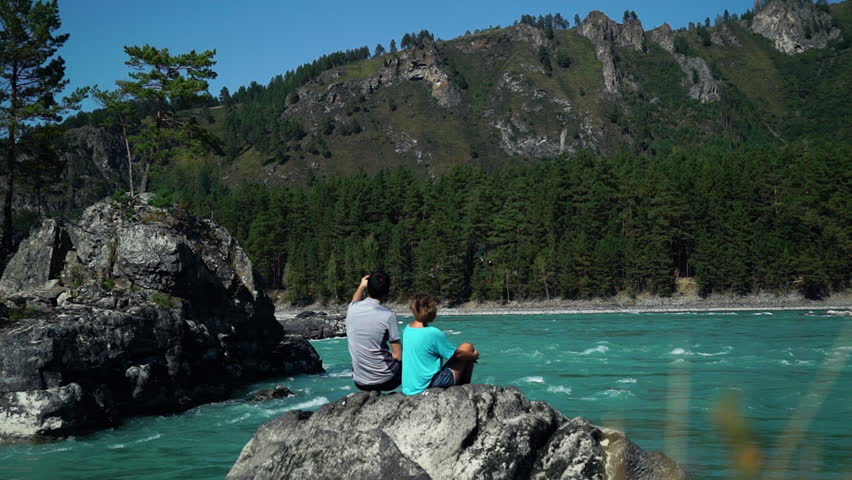 Two young people sit by the fast mountain river and take a self photo. Back view | Shutterstock HD Video #1018578880