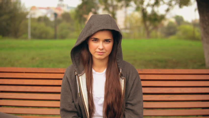 Young woman wearing casual hoodie sitting on the bench in park looking at the camera. | Shutterstock HD Video #1018639630