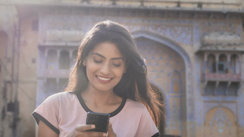 A beautiful smiling girl walking on a city street and using mobile phone while flock of pigeons flying in the background. A moving and back lit shot of an attractive woman on a smartphone smiles
