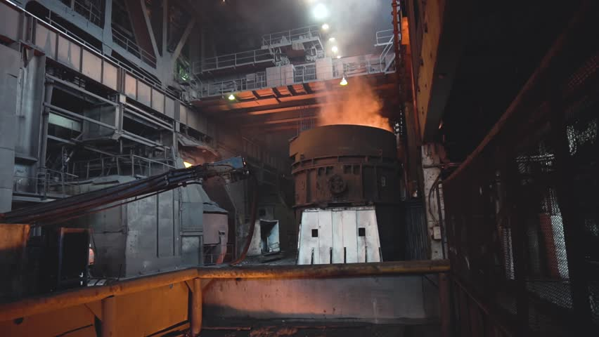 View of smelting of metal with ladle inside foundry. Footage. Interior of dirty metallurgical plant in dark. Concept of heavy industry | Shutterstock HD Video #1018674580
