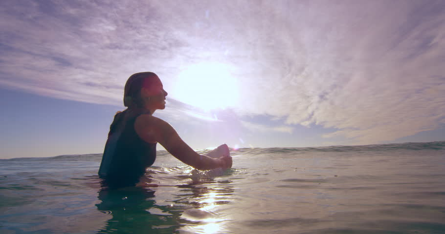 Contemplative young female surfer sitting on surfboard and swimming over ocean wave in Australian beach with bright day lighting. Medium shot on 4k RED camera. | Shutterstock HD Video #1018684030