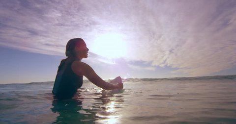 Contemplative young female surfer sitting on surfboard and swimming over ocean wave in Australian beach with bright day lighting. Medium shot on 4k RED camera.