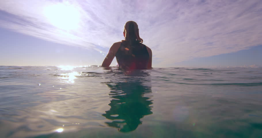 Fit female surfer swimming on surfboard looking out towards the calm ocean in Australia beach with bright day lighting. Medium to Wide shot on 4k RED camera. | Shutterstock HD Video #1018685200