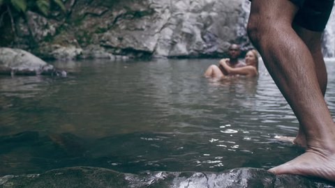 Man dives into lagoon while young beautiful couple swim holding each other in secluded river near waterfall in Australia in sunlight. Wide shot on 4k RED camera.