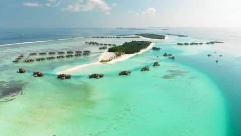 Aerial view to villas in maldives islands. Islands resorts in ocean. Aerial video from Maldives