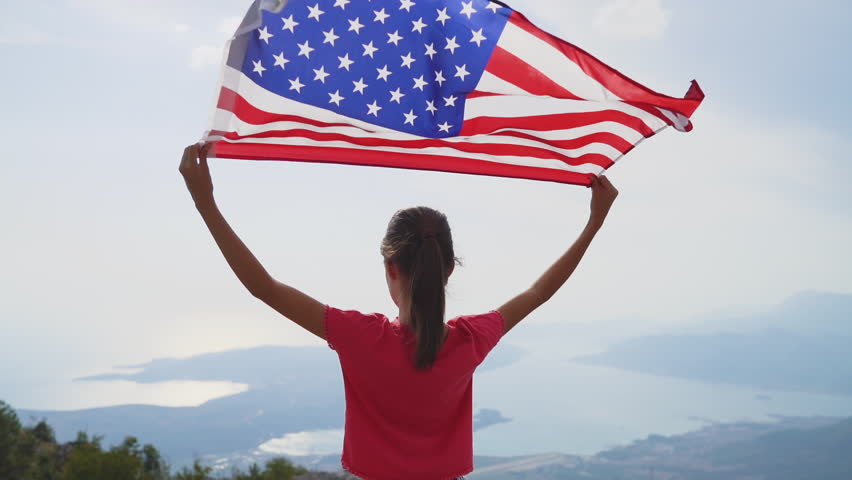 Child girl is waving American flag on top of mountain at sky background. Footage in slow motion #1018699000