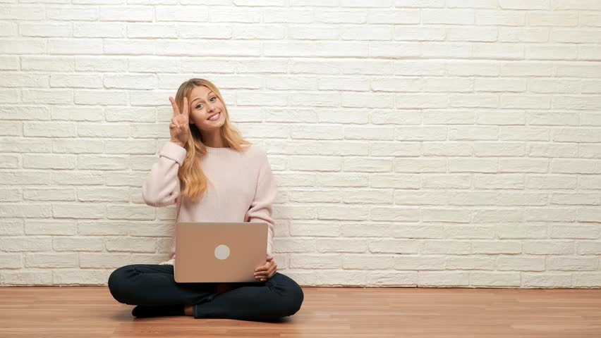 Young pretty blonde woman sitting at floor fun and happy, positive and natural, doing a gesture of victory, peace concept