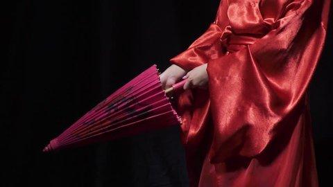 Beautiful geisha girl opens her umbrella and smiles