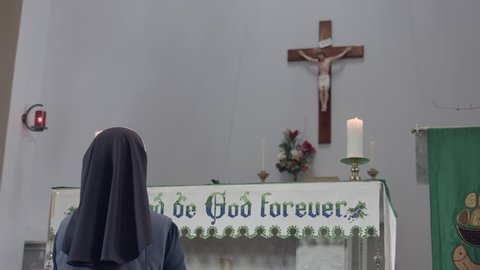 Religious sister holding rosary beads and kneeling in front of church altar with crucifix above on wall.