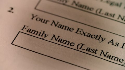 A pen writes in a family / last name on a census or US immigration document
