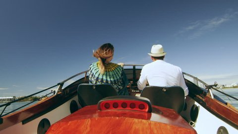 Happy millennial couple, wearing sunglasses smiling, cruising on a motorboat, wind in her hair, near the beach under a sunny blue sky. Close to wide shot on 4K RED camera with lens flare.