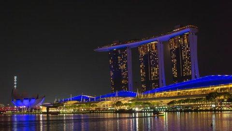 SINGAPORE, MARINA BAY - CIRCA OCTOBER 2018: Marina Bay Sands Light Show Time Lapse At Night During Full Moon With Boats Cruising On Marina Bay